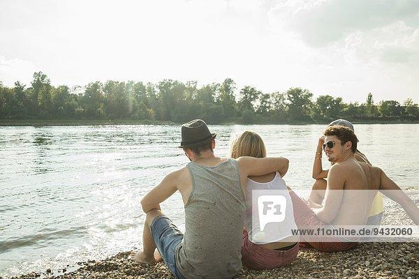 Vier junge Freunde sitzen am Seeufer