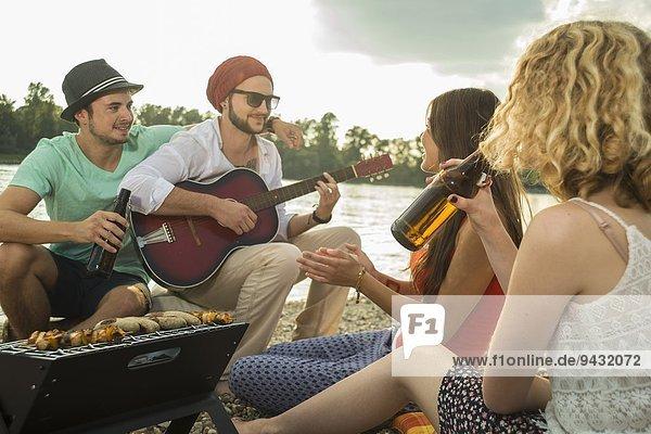 Junger Mann mit Freunden beim Gitarrespielen