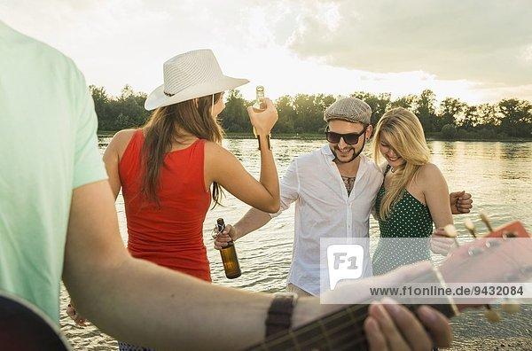 Freundeskreis mit Bier  Gitarre im Vordergrund