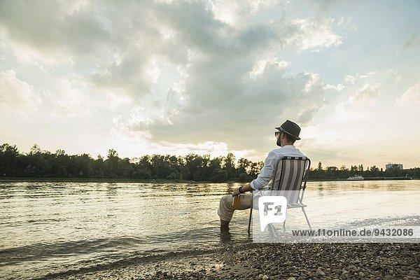 Junger Mann auf Stuhl am Seeufer sitzend