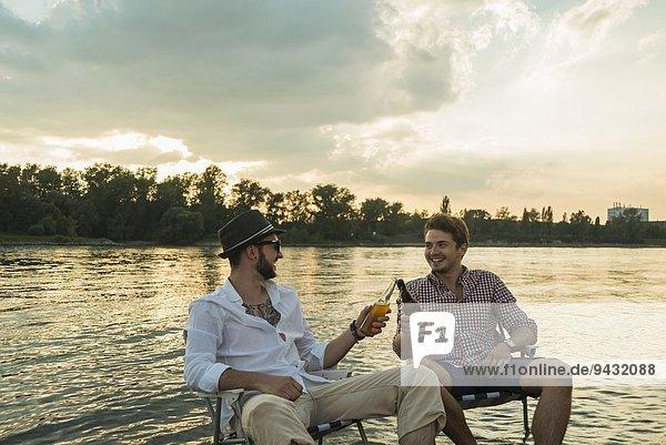 Junge Männer toasten mit Bierflaschen am See