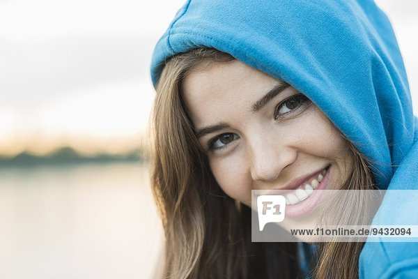 Young woman wearing blue hooded top