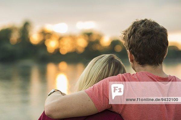 Junges Paar  Mann mit Arm um Frau  Rückansicht
