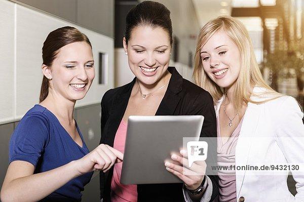 Geschäftsfrauen tauschen Informationen auf digitalen Tabletts aus