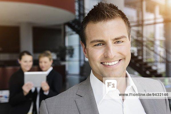 Lächelnder Geschäftsmann  Kollegen im Hintergrund mit digitalem Tablett