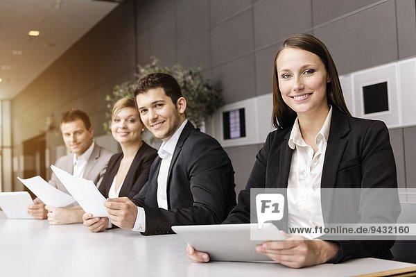 Geschäftsleute mit digitalem Tablett am Besprechungstisch