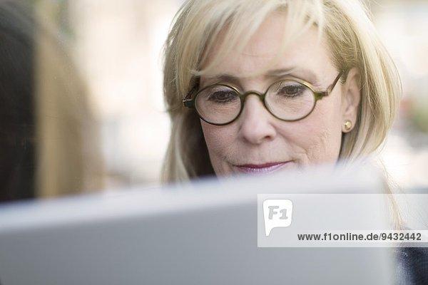 Reife Geschäftsfrau mit digitalem Tablett