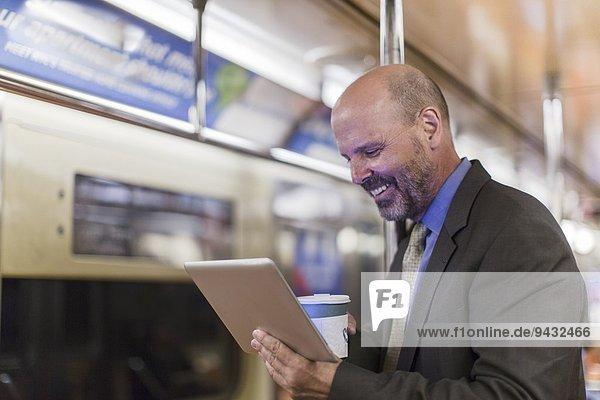 Erwachsener Mann in der U-Bahn mit digitalem Tablett