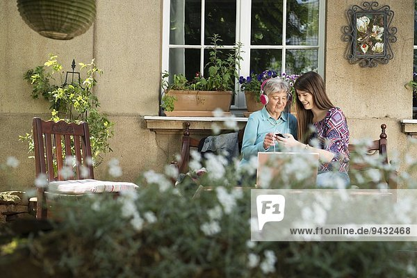 Young woman listening to music with grandmother