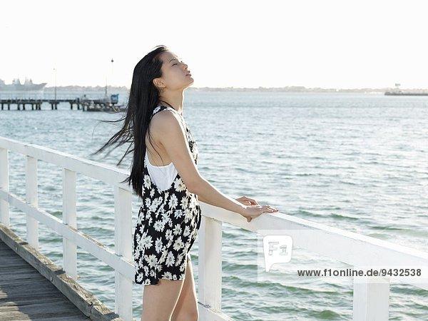 Junge Frau blickt vom Pier  Port Melbourne  Melbourne  Victoria  Australien