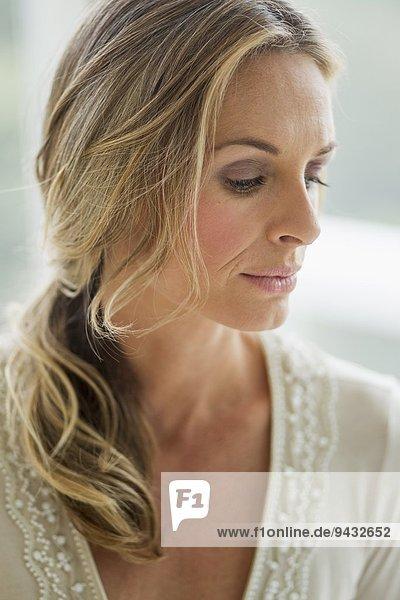 Reife blonde Frau mit Blick nach unten  Porträt