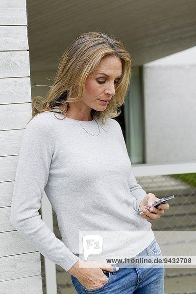 Reife Frau mit dem Handy