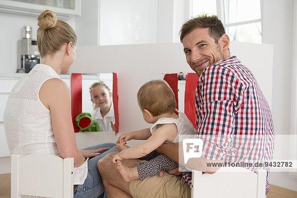 Mädchen beim Puppenspiel für die Familie