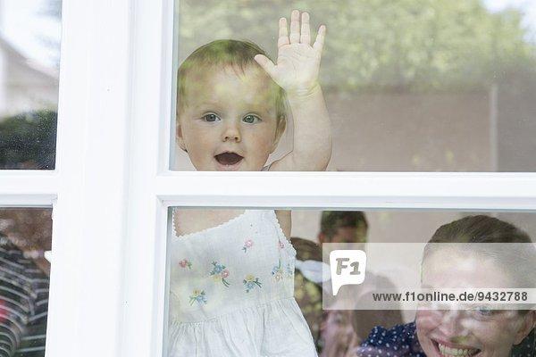 Mädchen und Mutter schauen aus dem Fenster.