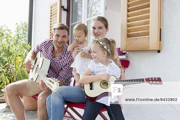 Vater spielt Gitarre mit Familie