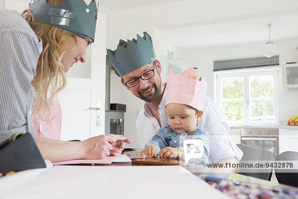 Eltern mit Baby-Tochter in hausgemachten Kronen