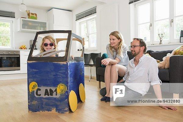 Eltern beobachten Tochter in hausgemachtem Spielzeugauto