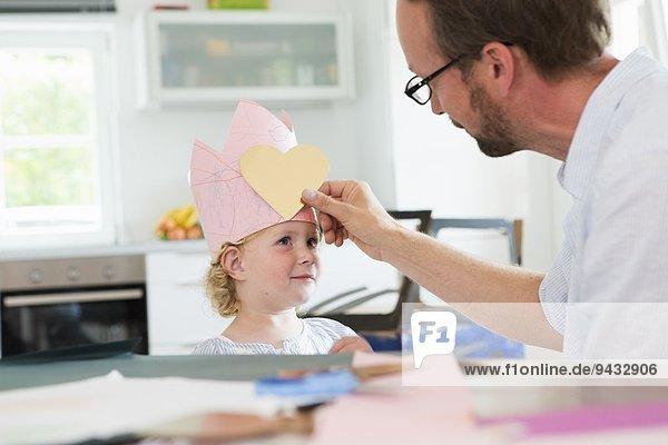 Vater legt Herzform auf die Papierkrone der Tochter