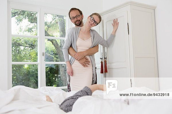 Paar im Schlafzimmer  Frau lehnt an Kleiderschrank