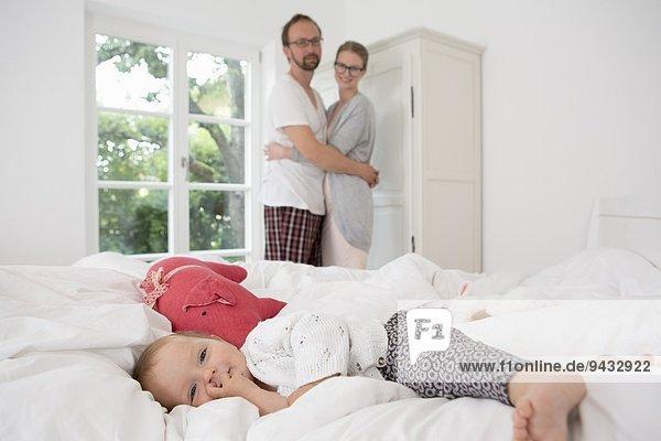 Kleines Mädchen auf dem Bett liegend  Eltern im Hintergrund