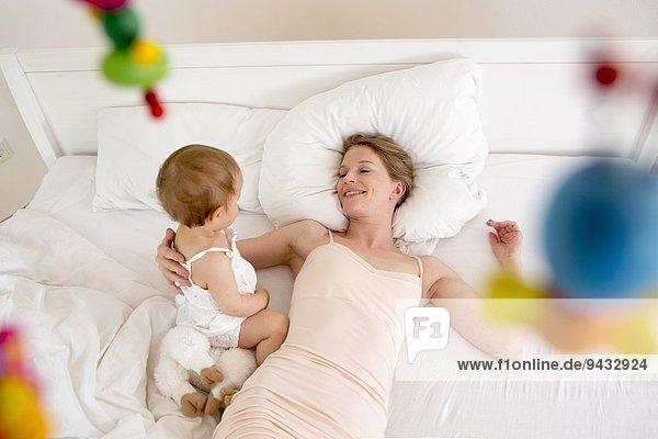 Mutter und Tochter auf dem Bett liegend  hoher Winkel