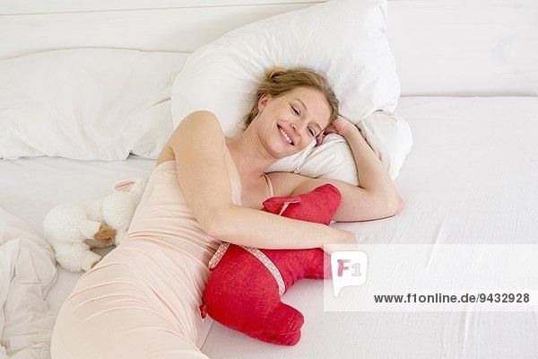 Mittlere erwachsene Frau  die auf dem Bett liegt und Plüschtier hält
