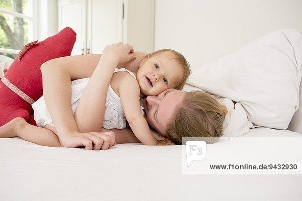 Mutter umarmt kleine Tochter auf dem Bett