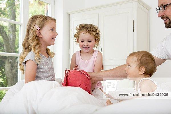 Drei Mädchen spielen auf dem Bett