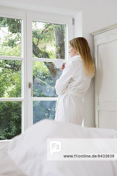 Mittlere erwachsene Frau im Bademantel mit Blick aus dem Fenster