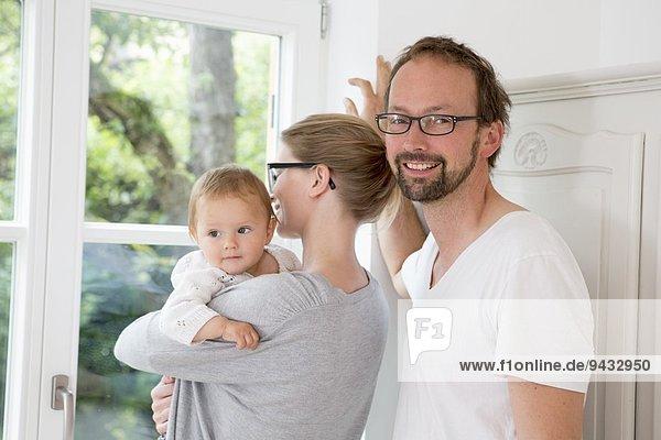 Mutter und Vater schauen aus dem Fenster mit der kleinen Tochter.
