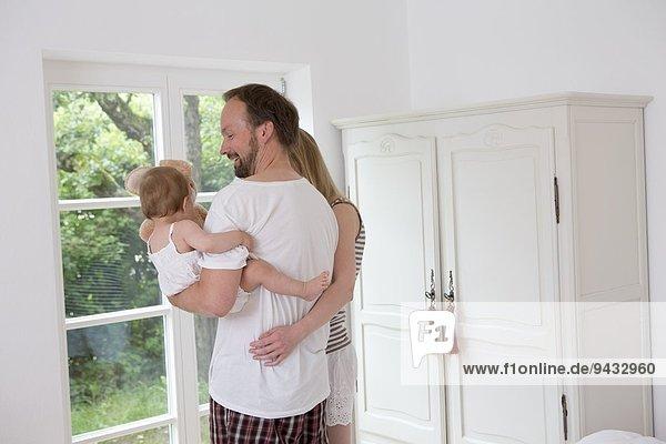 Vater hält Baby-Tochter  Frau mit Arm um Mann