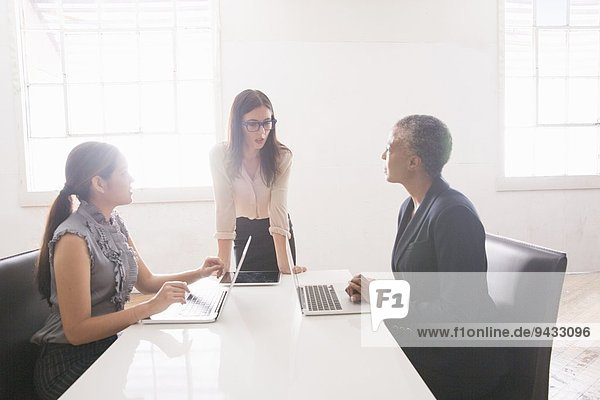 Businesswomen sitting at table with manager