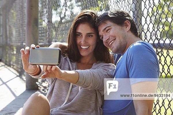 Junges Paar nimmt Selfie am Drahtzaun auf