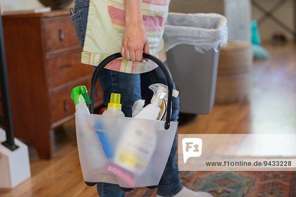 Junge Frau beim Putzen zu Hause mit grünen Reinigungsmitteln