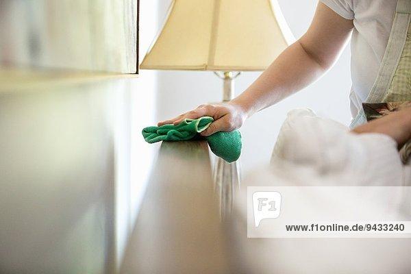 Junge Frau reinigt Oberflächen mit grünen Reinigungsmitteln