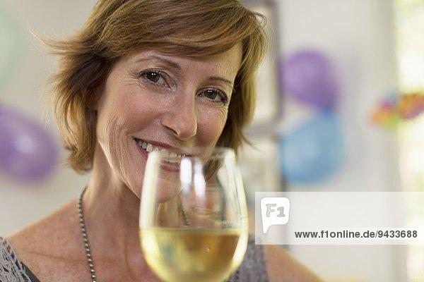 Porträt einer reifen Frau mit einem Glas Wein
