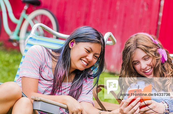 Two teenagers wearing headphones  listening to music  outdoors