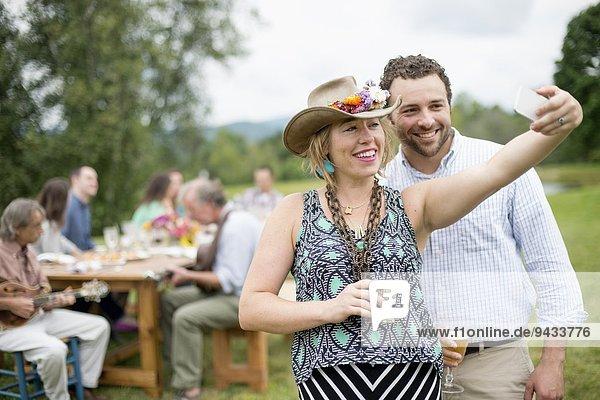 Mann und Frau beim Selbstporträt mit dem Smartphone  während Freunde der Familie hinter dem Tisch sitzen  im Freien
