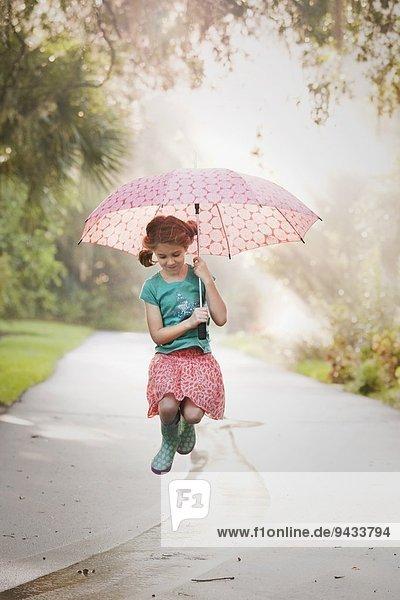Mädchen hält Regenschirm hoch und springt Pfützen auf die Straße