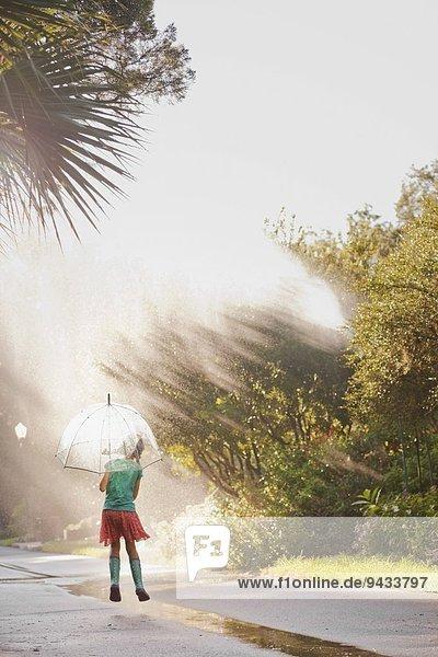 hoch,oben,Regenschirm,Schirm,Straße,halten,springen,Pfütze,Rückansicht,Ansicht,Mädchen