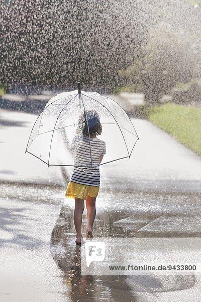 Rückansicht des barfüßigen Mädchens mit Regenschirm beim Spaziergang durch die Straßenpfütze