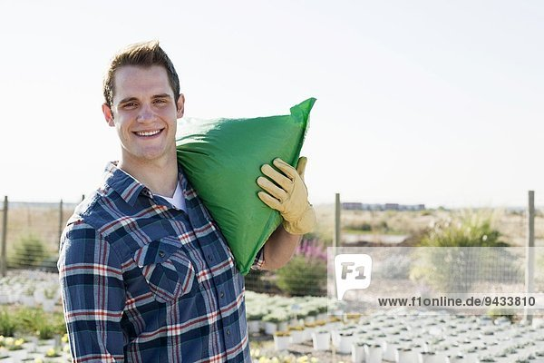 Portrait of young male worker carrying sack on shoulders at plant nursery