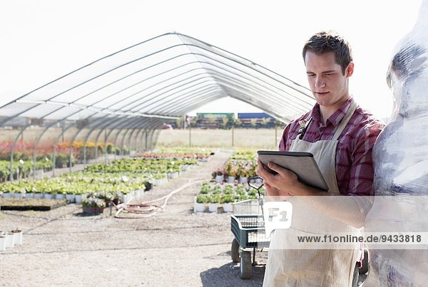Young male horticulturalist using digital tablet at plant nursery
