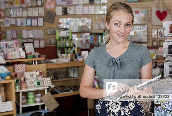 Portrait of female sales assistant using digital tablet in stationery shop