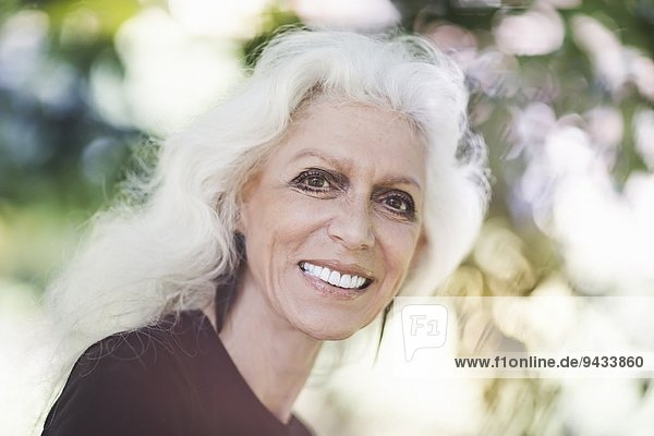 Grauhaarige Frau lächelt selbstbewusst