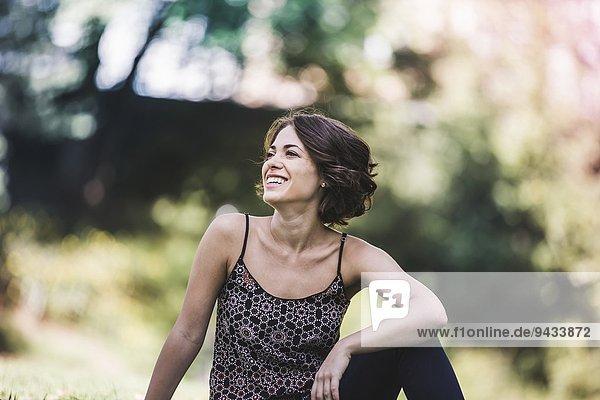Junge Frau entspannt sich im Stadtpark und lacht.