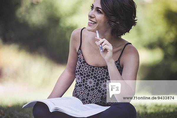 Young woman sitting in city park studying textbook
