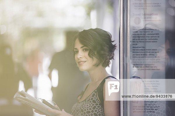 Junge Frau an der Bushaltestelle Zeitung lesen und auf den Bus warten  New York  USA Junge Frau an der Bushaltestelle Zeitung lesen und auf den Bus warten, New York, USA