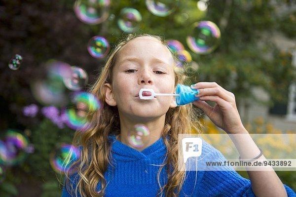 Mädchen bläst Blasen im Garten