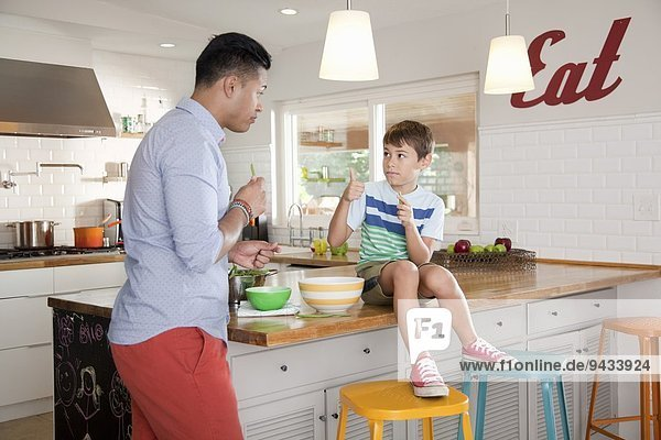 Vater und Sohn in der Küche  Junge auf der Theke sitzend